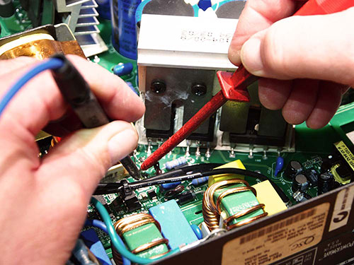 A pair of mans hands working on the internals of a stereo system.